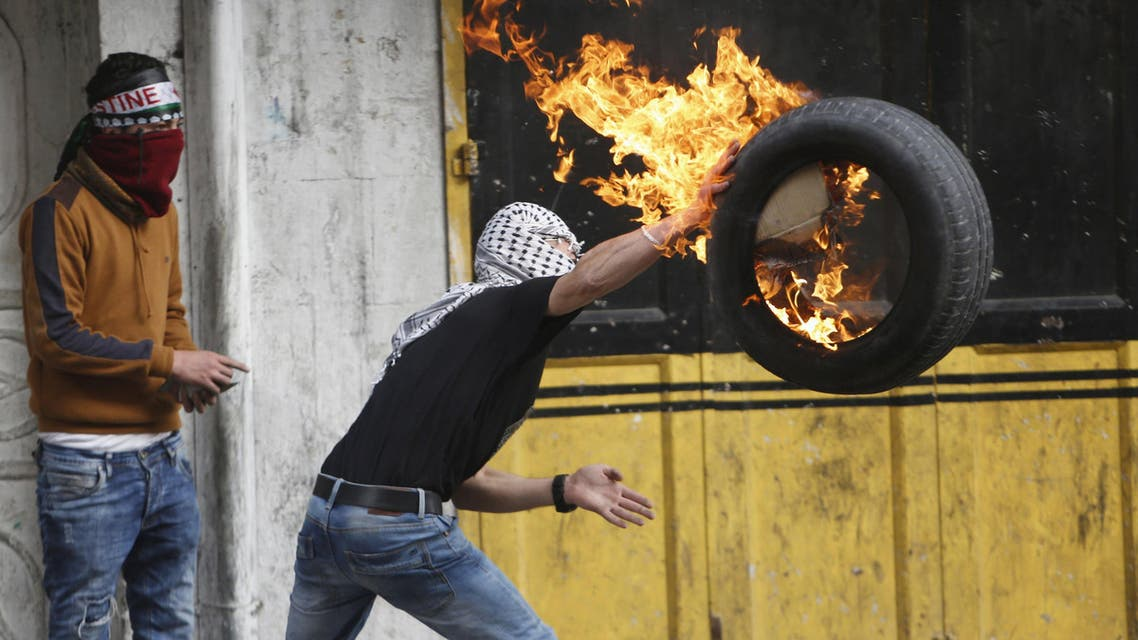 A Palestinian protester throws a burning tyre during clashes with Israeli troops following a protest  in the West Bank city of Hebron Nov. 4, 2015.  (Reuters)