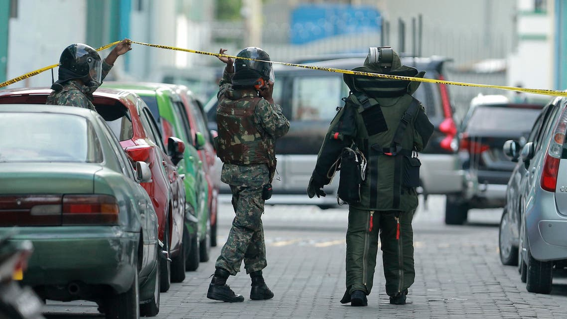 Police and Maldives National Defense Force (MNDF) personnel cordon off an area suspecting an explosive inside the engine compartment of a parked broken car in Male, Maldives, Wednesday, Nov. 4, 2015. The same was later confirmed to be a hoax call.The president of the Maldives declared a state of emergency on Wednesday that sharply curtails key rights of citizens for 30 days following an explosion on his speedboat and the discoveries of a homemade bomb near his residence and a weapons cache. (AP Photo/Mohamed Sharuhaan)
