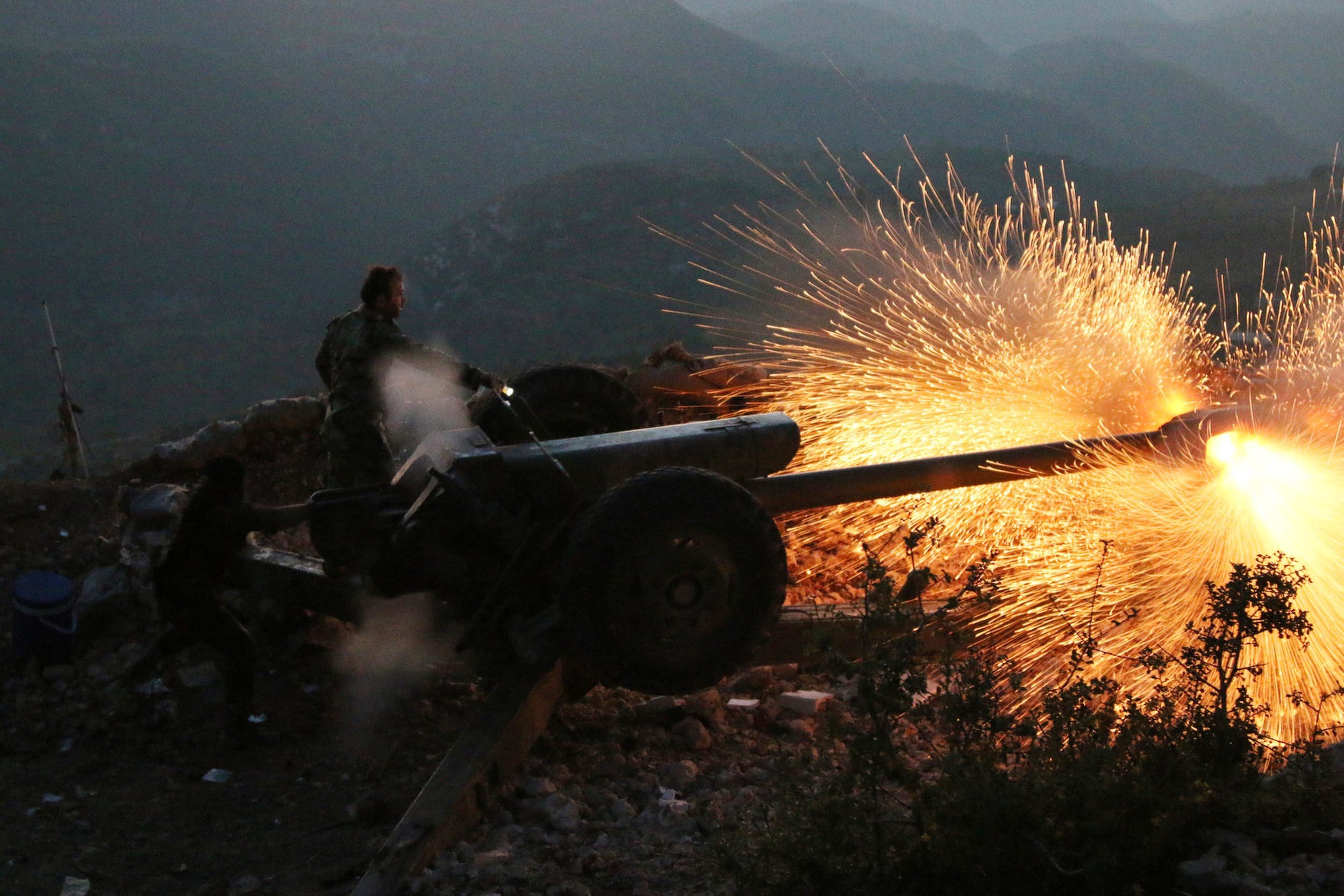 In this photo taken on Saturday, Oct. 10, 2015, Syrian army personnel fire a cannon in Latakia province, about 12 from the border with Turkey in Syria.  (AP)