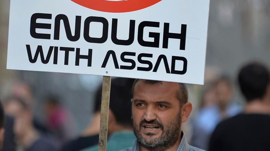 A demonstrators holds a placards with a picture depicting Syrian President Bashar Assad, during a protest against Russian military operations in Syria, in Istanbul. (AP)
