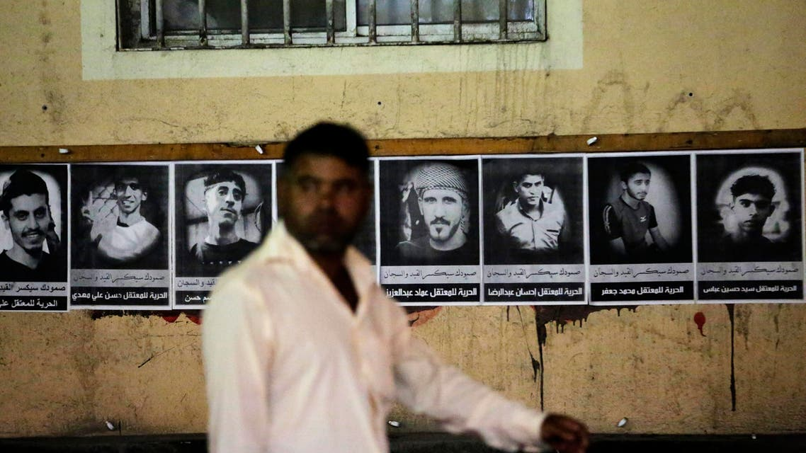 An Asian worker walks past images of political prisoners plastered on a wall in Malkiya village, Bahrain, Wednesday, Nov. 4, 2015. Bahrain says it has arrested 47 suspects and seized explosives in a counter terrorism operation, and has again alleged Iranian involvement in militant attacks. (AP Photo/Hasan Jamali)
