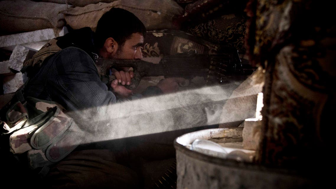 In this Tuesday, Nov. 23, 2014 photo, a Kurdish fighter fires on an Islamic State group position in Kobani, Syria.