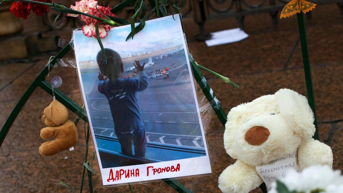 A portrait of 10 month old Darina Gromova, daughter of young family of Alexei Gromov, 27, his wife Tatyana, 26, victims of a plane crash, attached to a fence surrounded by flowers and toys at Dvortsovaya (Palace) Square in St.Petersburg, Russia, Wednesday, Nov. 4, 2015. AP