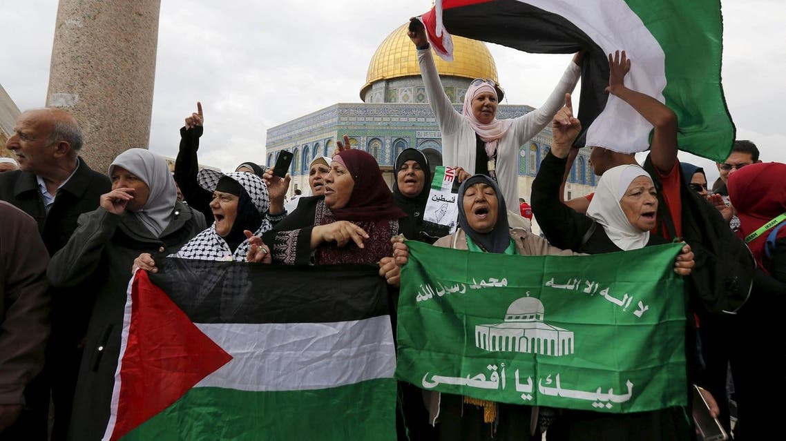 Women hold Palestinian flags and a Hamas flag during a protest after Friday prayers in Jerusalem's Old City. (Reuters)