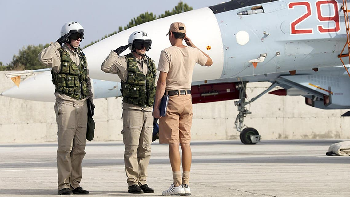 A ground crew member reports to pilots that their Sukhoi Su-30 fighter jet is ready for a combat mission at Hmeymim air base near Latakia, Syria, in this handout photograph released by Russia's Defence Ministry, October 22, 2015.