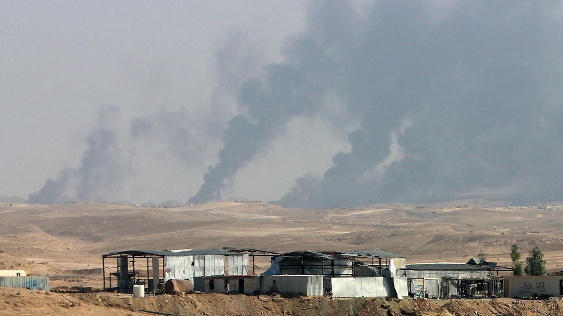 In this Saturday, Oct. 24, 2015 photo, smoke rises as Iraqi security forces and allied Popular Mobilization Forces shell Islamic State group positions at an oil field outside Beiji, some 250 kilometers (155 miles) north of Baghdad, Iraq. Coalition officials said that Iraqi security forces, backed by the paramilitary forces and Iraqi federal police, and supported by airstrikes, continue to work to recapture and clear the western city of Ramadi and the city of Beiji, home to Iraq's largest oil refinery. (AP Photo)