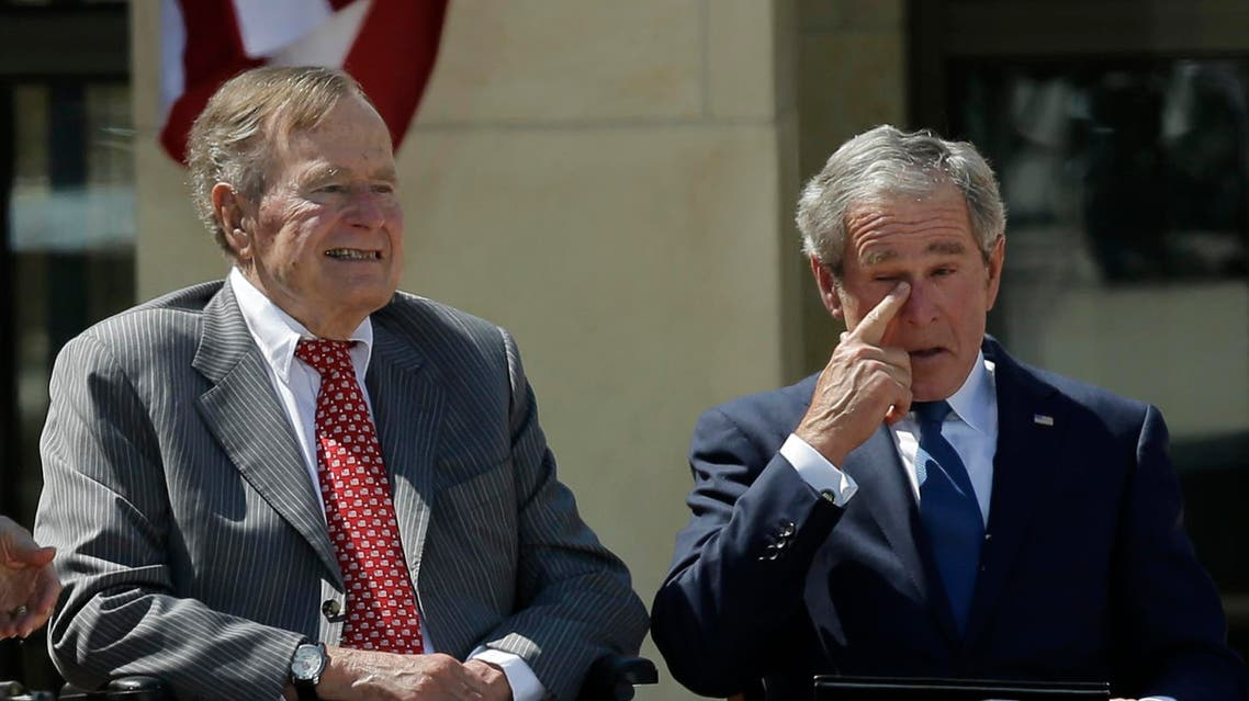 Former president George W. Bush wipes a tear after his speech during the dedication of the George W. Bush Presidential Center Thursday, April 25, 2013, in Dallas. Former president George H.W. Bush is at left. (AP Photo/David J. Phillip)