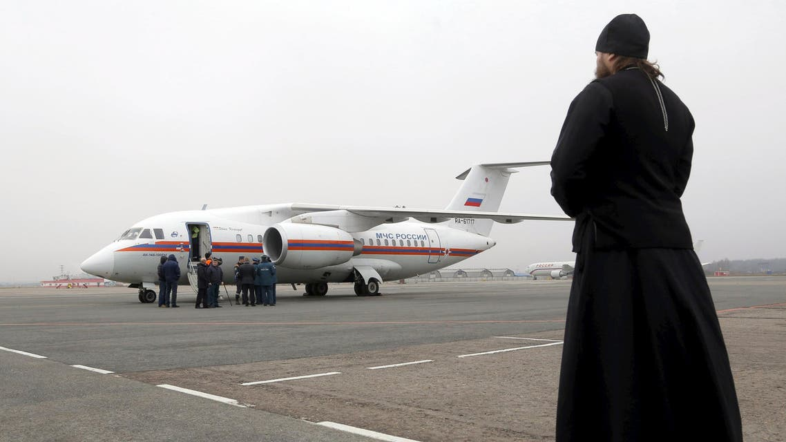 An Orthodox priest looks at a Russian emergencies ministry's plane, carrying the remains of victims of the plane crash in Egypt, shortly after its landing on the airfield of Pulkovo airport outside St. Petersburg, Russia, November 6, 2015. (REUTERS