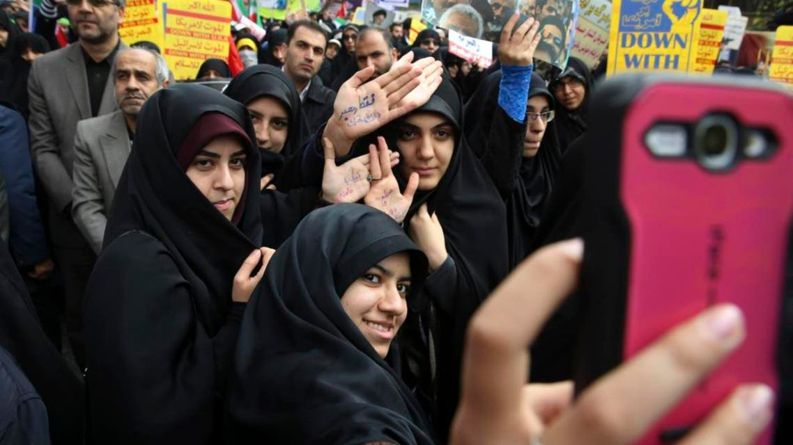 Female Iranian demonstrators take a selfie while showing their hands with slogans in support of the Supreme Leader Ayatollah Ali Khamenei during an annual rally in front of the former U.S. Embassy in Tehran. (AFP)
