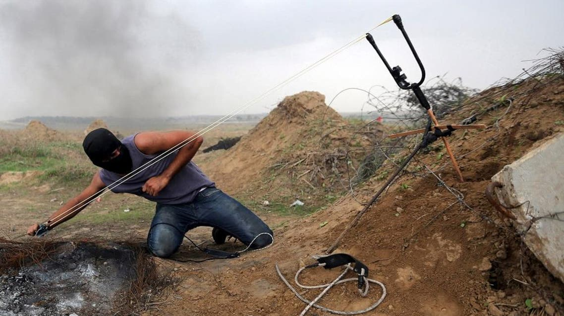 A Palestinian protester uses sling shot to hurl stones at Israeli troops during clashes near border between Israel and Central Gaza Strip November 6, 2015. (Reuters)