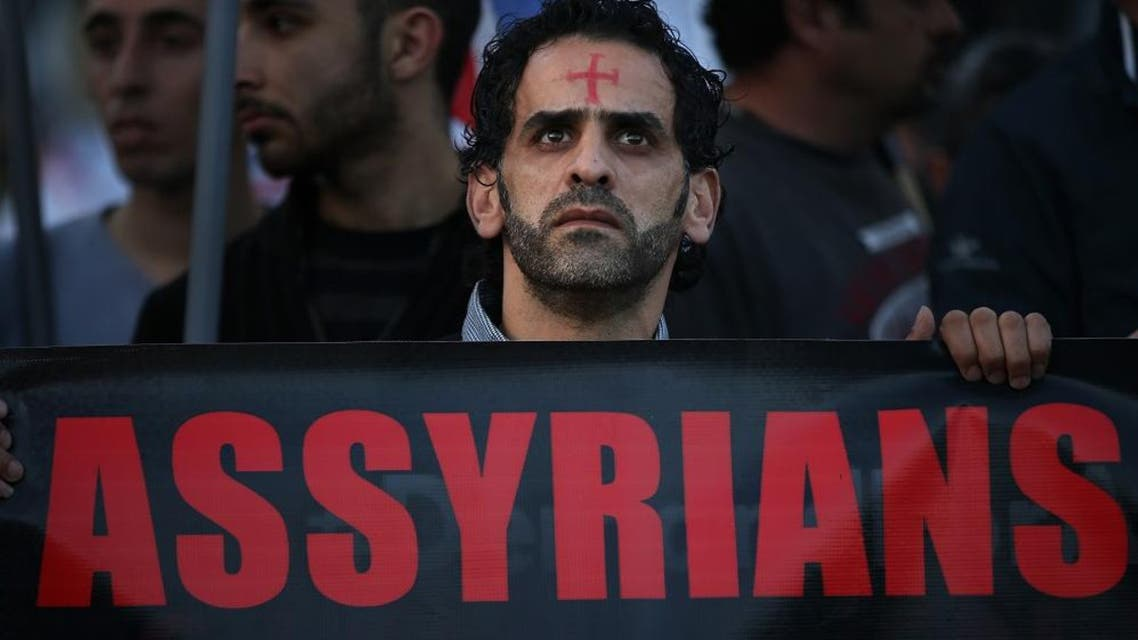 an Assyrian man with a red cross painted on his forehead holds a banner as he walks during a protest of several hundred people in solidarity with Christians abducted in Syria and Iraq. (File: AP)