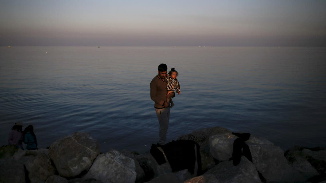 A Syrian refugee holds a baby at the port of Mytilene on the Greek island of Lesbos