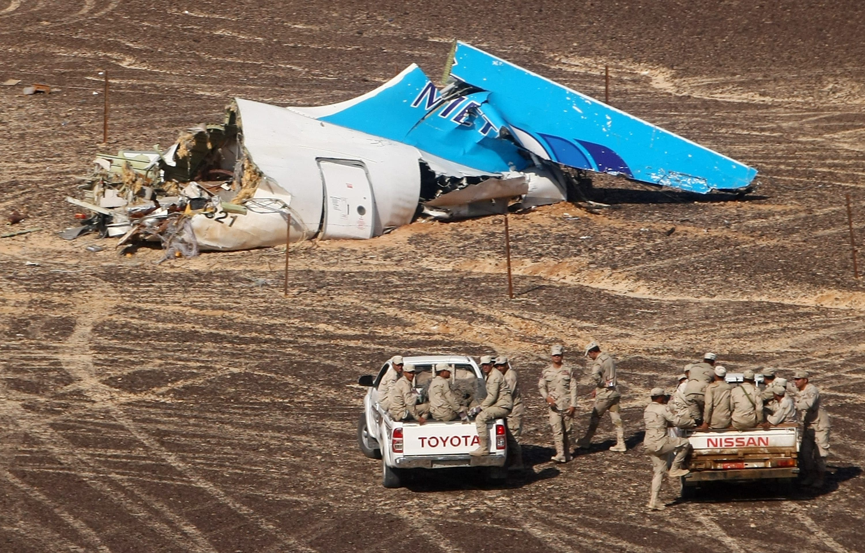 In this photo made available Monday, Nov. 2, 2015, and provided by Russian Emergency Situations Ministry, Egyptian Military on cars approach a plane's tail at the wreckage of a passenger jet bound for St. Petersburg in Russia that crashed in Hassana, Egypt, on Sunday, Nov. 1, 2015.
