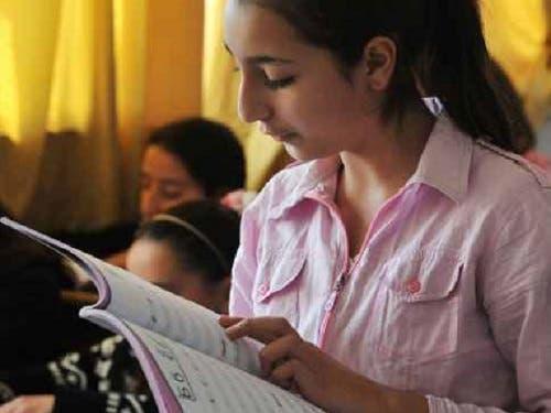 طالبة تقرأ مقررا من اللغة الروسية في اللاذقية