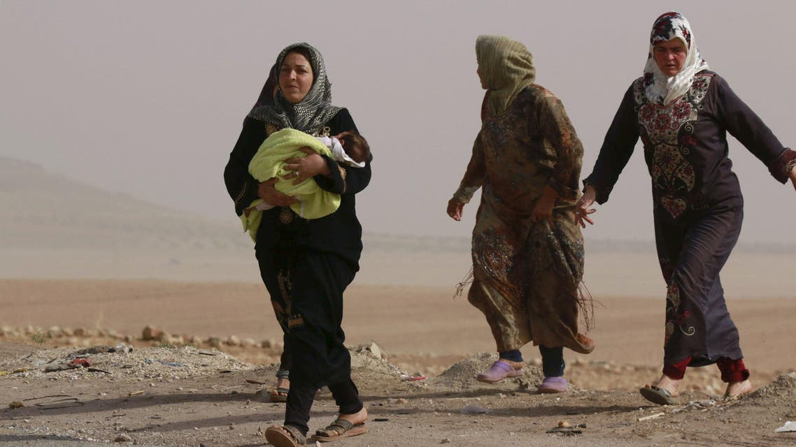 Internally displaced women who fled the violence in Abteen village walk along a street in Mraykes village in the southern countryside of Aleppo, Syria October 21, 2015. Fighting in Syria has displaced 35,000 people from Hader and Zerbeh on the southwestern outskirts of the city of Aleppo in the past few days, the U.N. Office for the Coordination of Humanitarian Affairs (OCHA) said on Monday. REUTERS/Hosam Katan FOR EDITORIAL USE ONLY. NO RESALES. NO ARCHIVE.