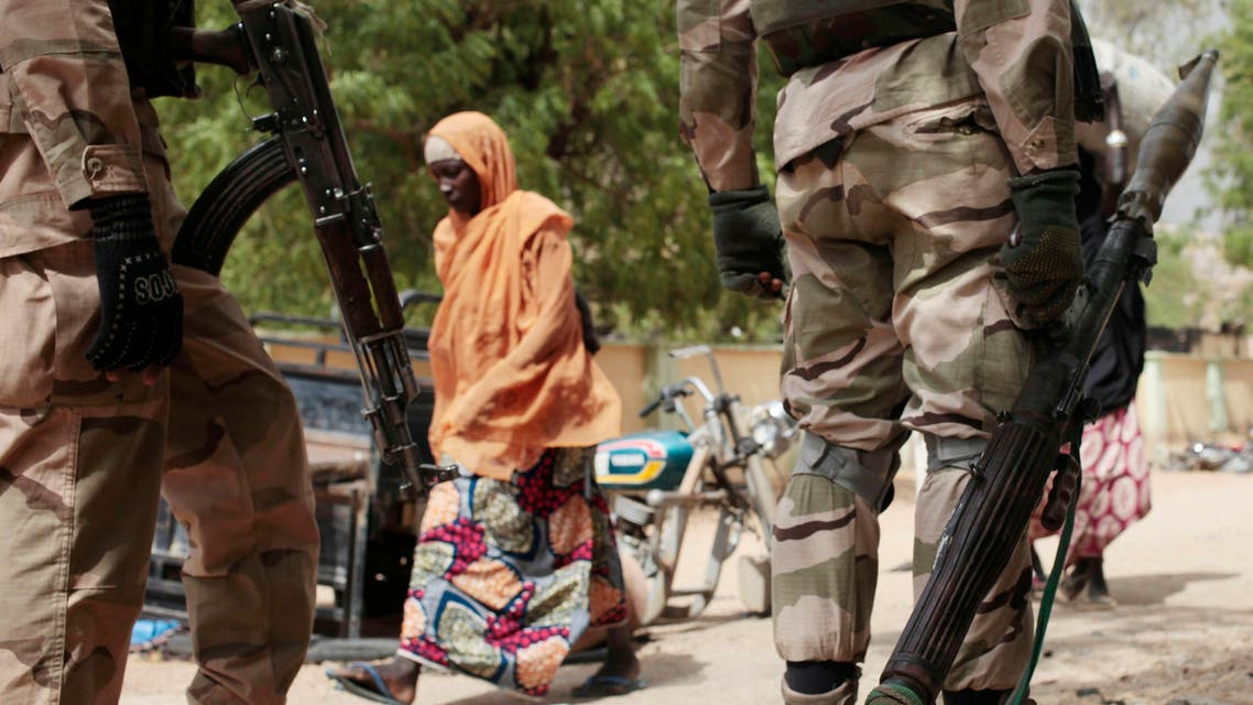 In this Wednesday April 8, 2015 file photo, a woman walks past Nigerian soldiers at a checkpoint in Gwoza, Nigeria, a town newly liberated from Boko Haram.