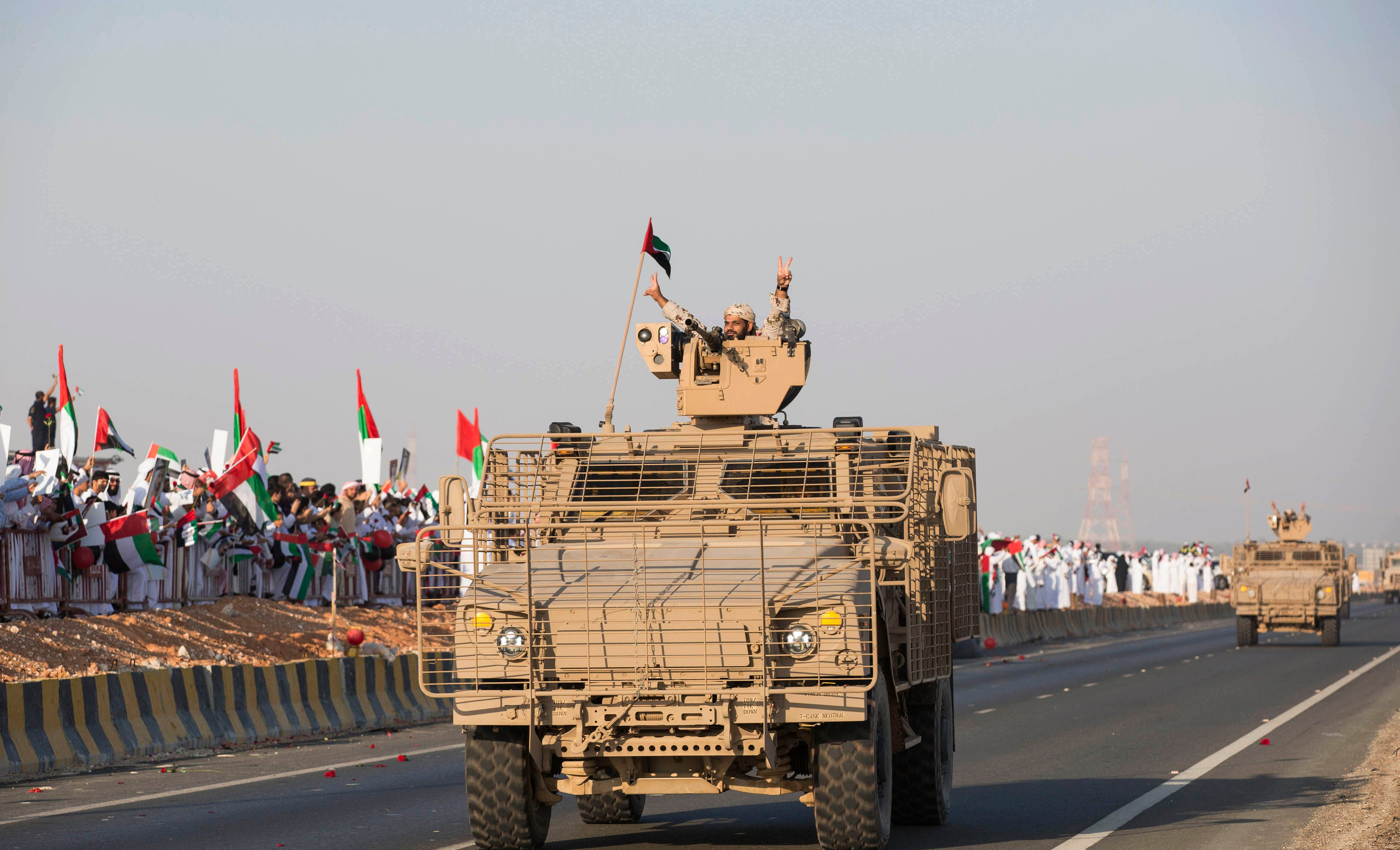 Emirati people wave the national flag as a convoy of UAE military vehicles and personnel travels from Al Hamra Military Base to Zayed Military City, marking the return of the first batch of UAE Armed Forces military personnel from Yemen, United Arab Emirates, Saturday, Nov. 7, 2015. (WAM/AP)