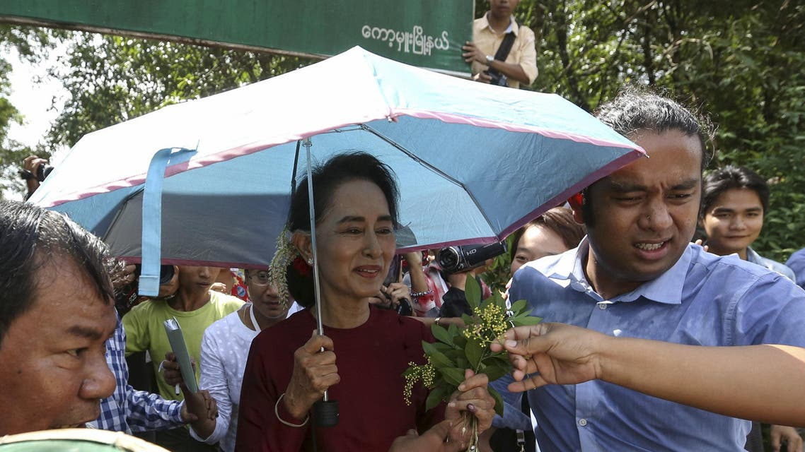 Myanmar pro-democracy leader Aung San Suu Kyi accepts flowers from supporters as she visits polling stations at her constituency town Kawhmu township November 8, 2015. REUTERS