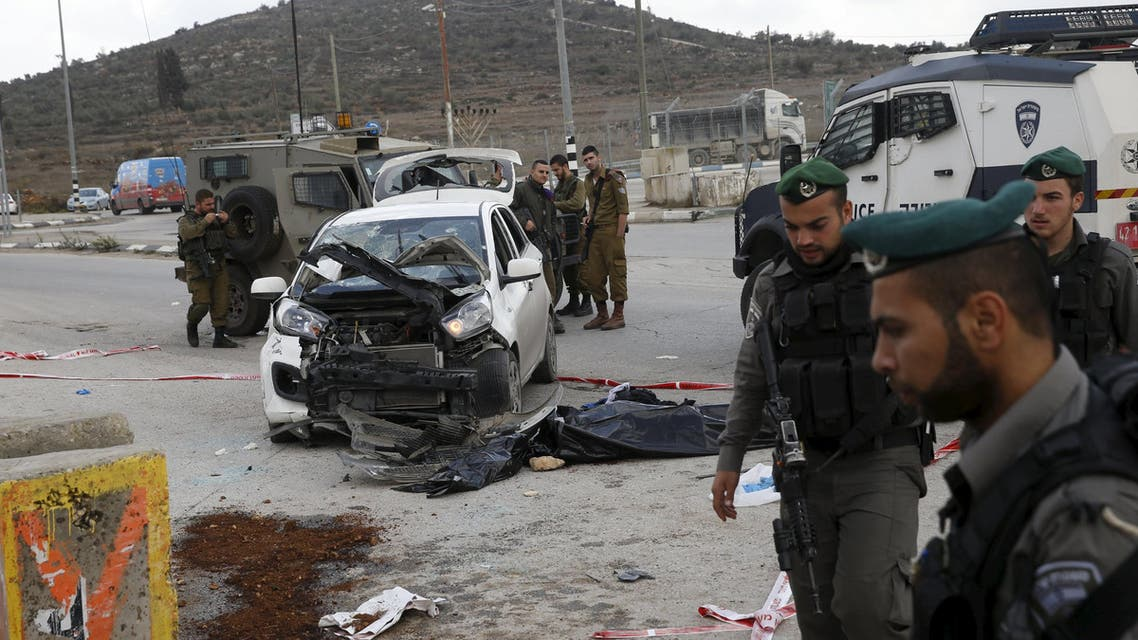 Israeli soldiers and paramilitary police stand near a covered body at the scene of a car-ramming near the West Bank Jewish settlement of Tapuach south of Nablus November 8, 2015. On Sunday, a Palestinian deliberately rammed his car into a bus stop near the Jewish settlement of Tapuach in the occupied West Bank, injuring four civilians, an Israeli police spokeswoman said. Paramilitary police troopers shot the man dead, she said. REUTERS/Baz Ratner