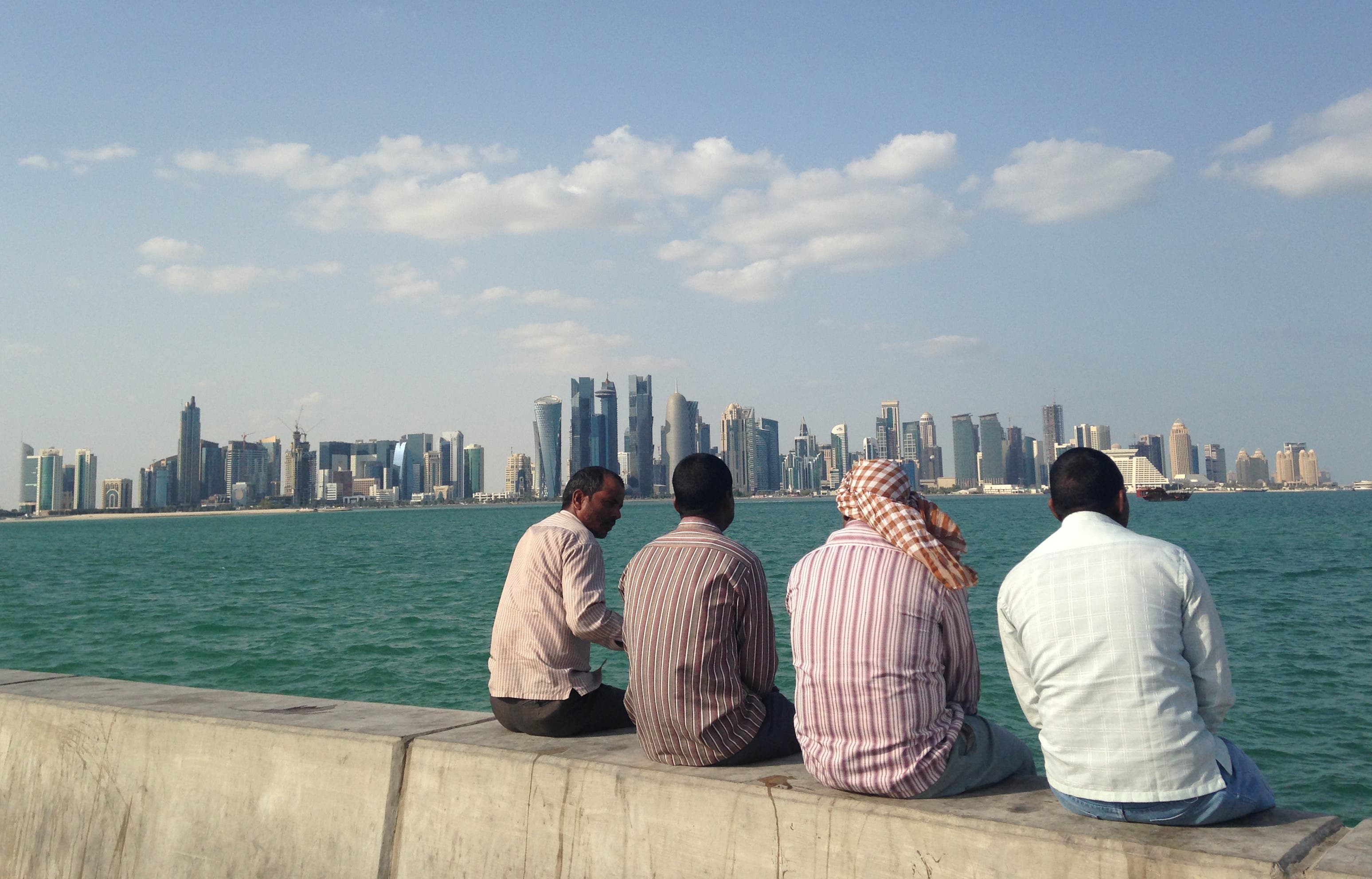 FILE - In this Nov. 7, 2014, file photo, men talk by the sea overlooking the Qatar skyline in Doha, Qatar. Amnesty International said Thursday, May 21, 2015, that Qatar is failing to deliver on reforms for its low-paid migrant workers a year after the wealthy Gulf nation announced plans to improve conditions for laborers building its highways, hotels, stadiums and skyscrapers. (AP Photo/Rob Harris, File)