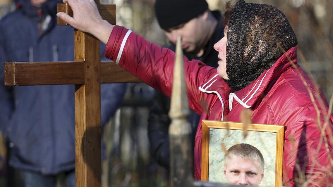 A relative reacts as she touches a cross on the grave of Alexei Alexeev, a victim of a Russian airliner which crashed in Egypt, during a funeral ceremony at the Bogoslovskoye cemetery in St. Petersburg, Russia November 5, 2015. An Airbus A321, operated by Russian airline Kogalymavia under the brand name Metrojet, crashed on Saturday shortly after taking off from the Red Sea resort of Sharm al-Sheikh on its way to St. Petersburg, killing all 224 people on board. REUTERS/Peter Kovalev