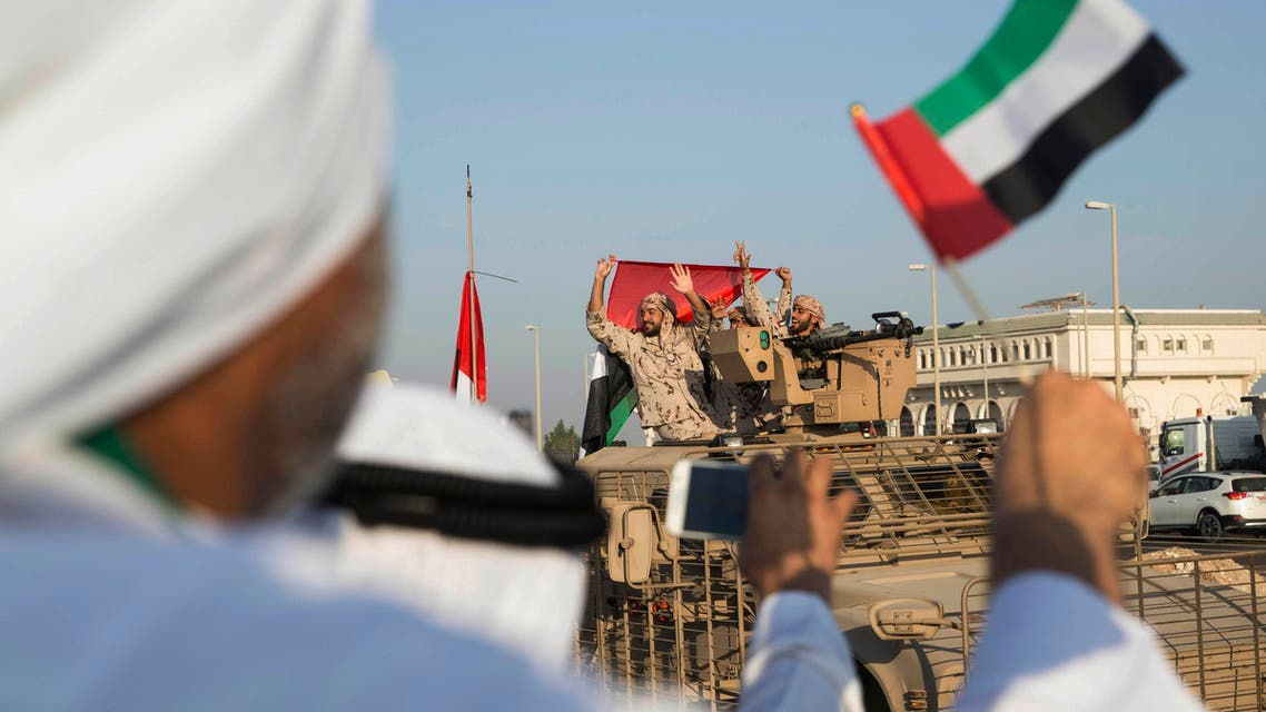 In this photo made available by the Emirates News Agency, WAM, Emirati people wave the national flag as a convoy of UAE military vehicles and personnel travels from Al Hamra Military Base to Zayed Military City, marking the return of the first batch of UAE Armed Forces military personnel from Yemen, United Arab Emirates, Saturday, Nov. 7, 2015. (WAM/AP)