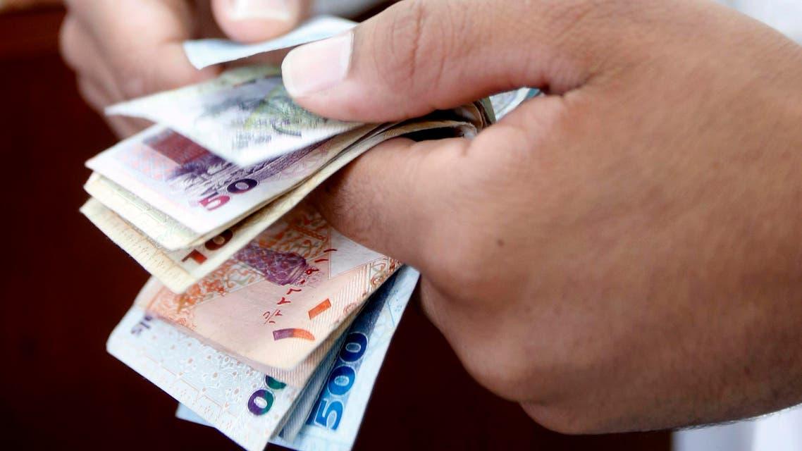 A man counts Qatari riyal at a money changer in Doha May 28, 2013.  (Reuters)