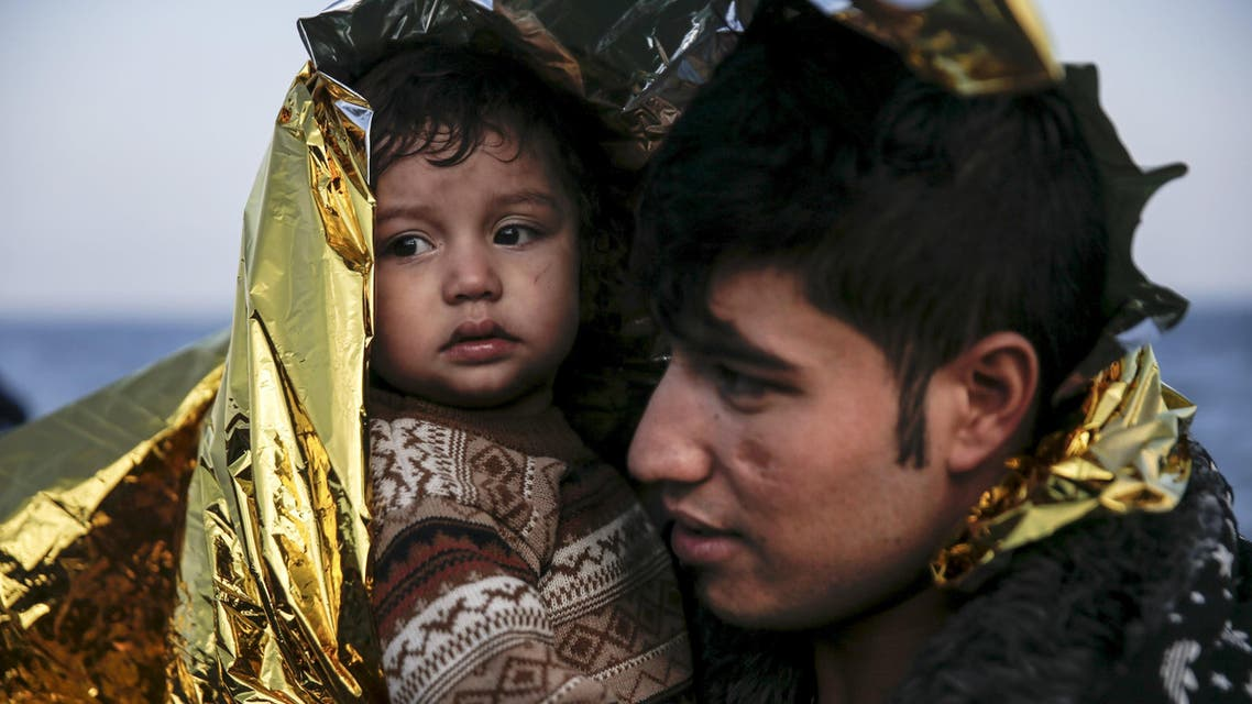 An Afghan refugee and his baby are covered with a thermal blanket, moments after arriving on a raft on the Greek island of Lesbos. (Reuters)