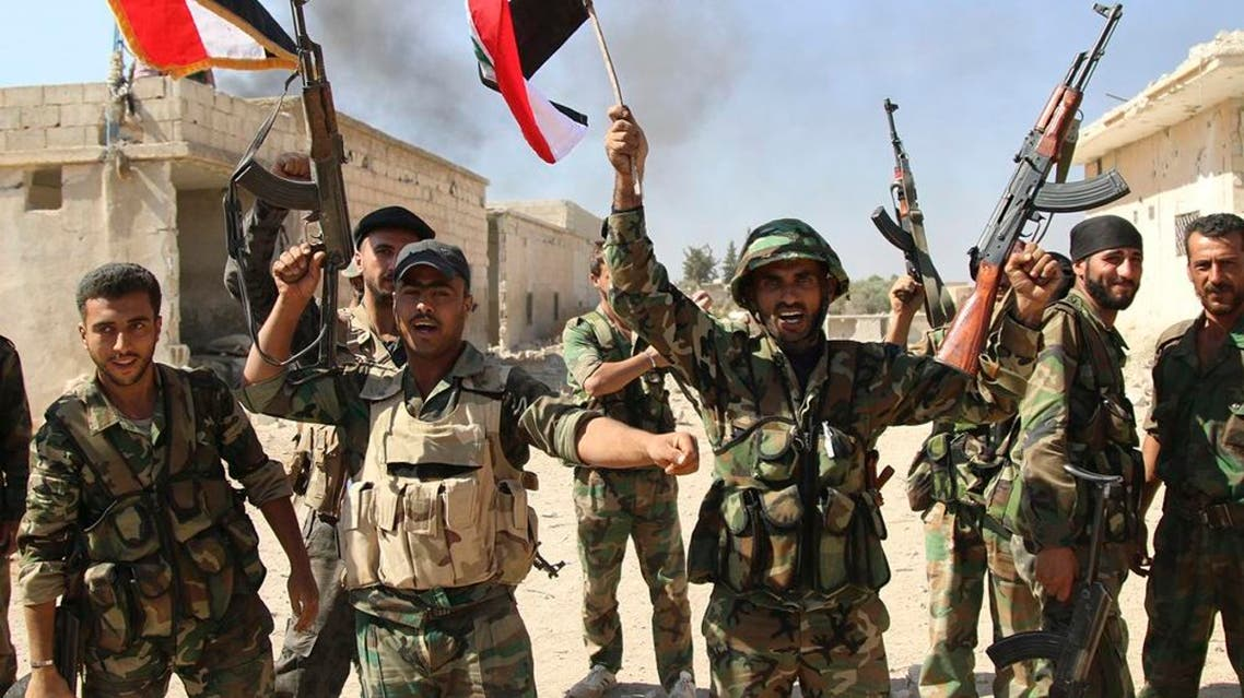 Syrian soldiers waving Syrian flags celebrate the capture of Achan, Hama province, Syria. (File: AP)