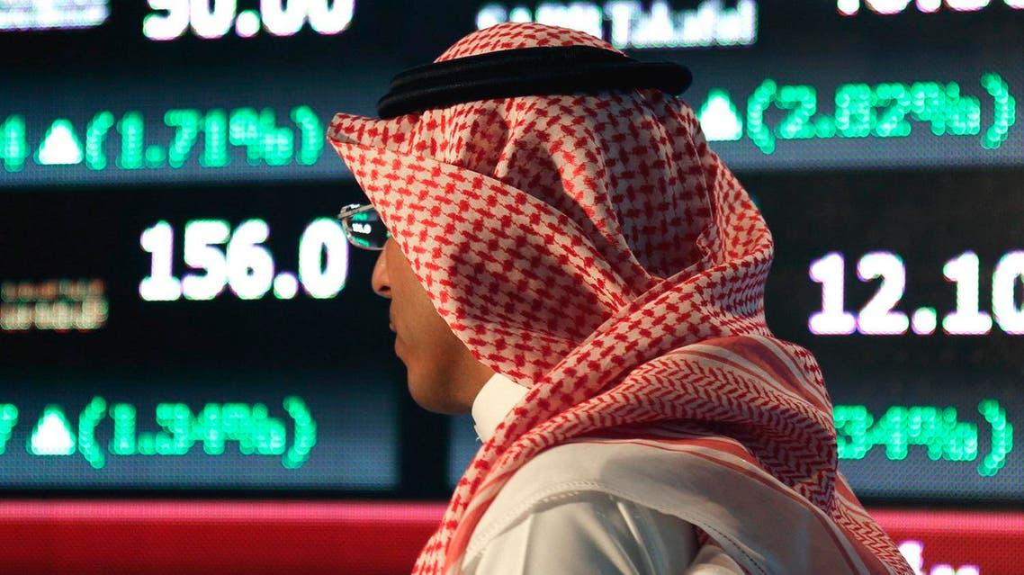A Saudi man walks at the Tadawul Saudi Stock Exchange, in Riyadh, Saudi Arabia. (File photo: AP)