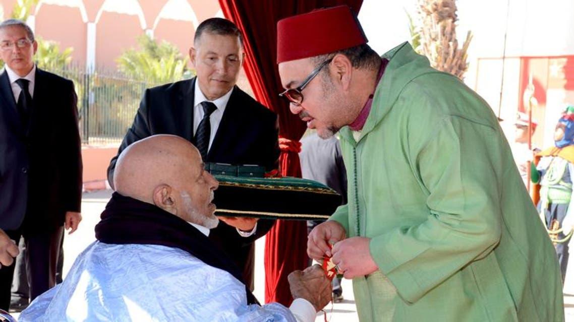العاهل المغربي خلال توشيحه لشيخ  صحراوي في مدينة العيون