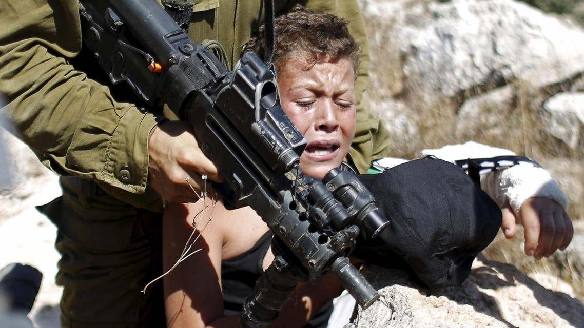 An Israeli soldier detains a Palestinian boy during a protest against Jewish settlements in the West Bank village of Nabi Saleh, near Ramallah August 28, 2015. (File photo: Reuters)