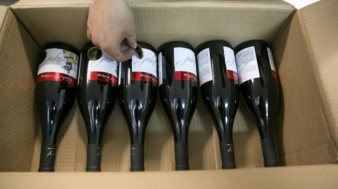A worker places stickers on wine bottles while packaging them for export at Shiloh Wineries, north of the West Bank city of Ramallah November 8, 2015. (Reuters)