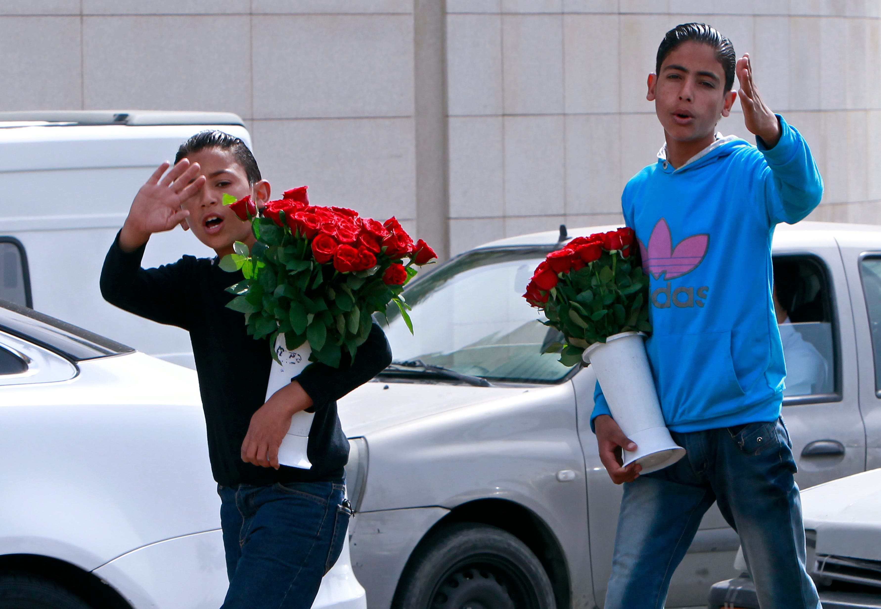 Two Syrian brothers Bashar, 12, left, and Rasem, 14, right, who fled their home from Hassakeh, try to sell flowers to make a living in Beirut, Lebanon, Wednesday, March 13, 2013. (AP)