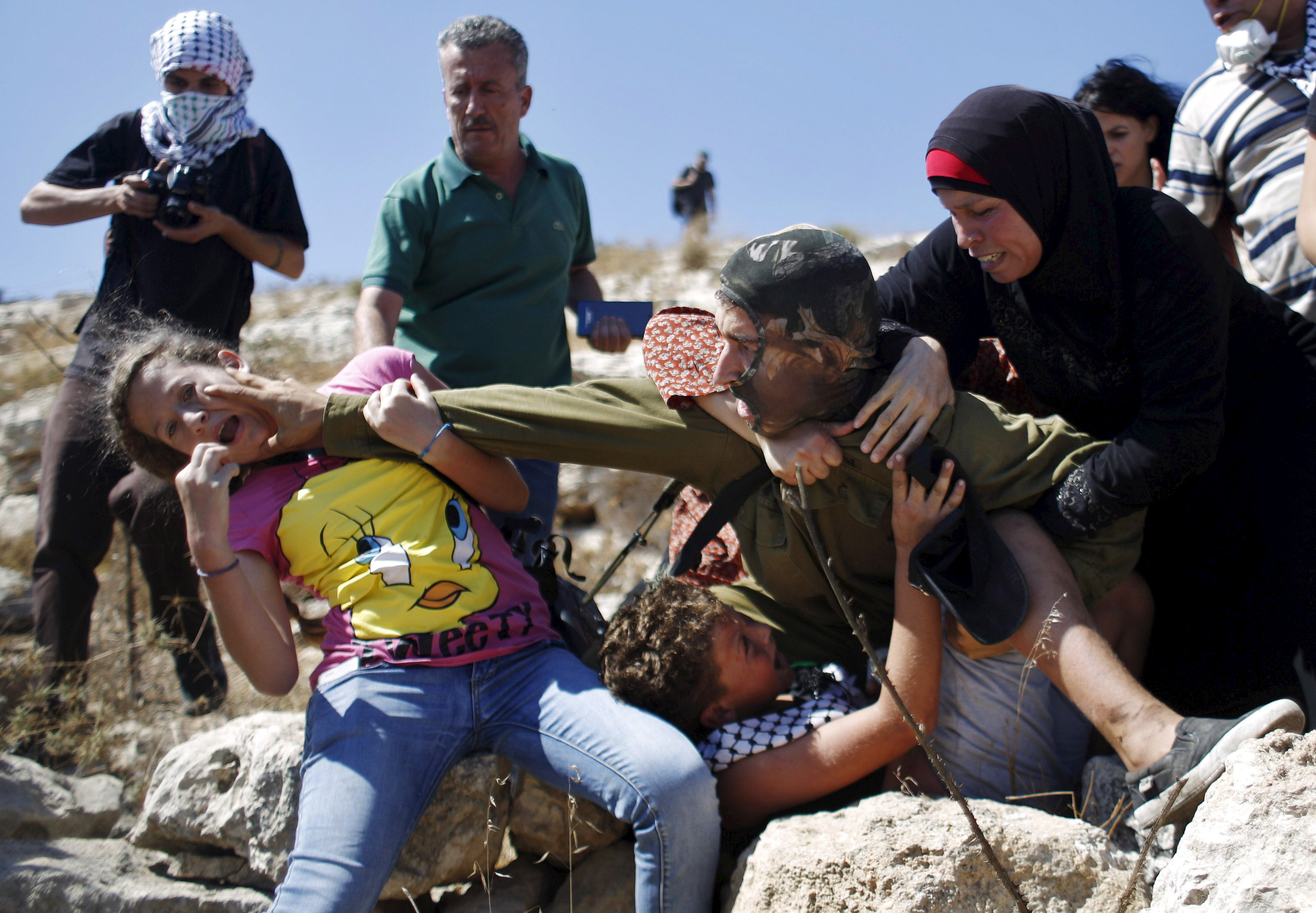 Palestinians scuffle with an Israeli soldier as they try to prevent him from detaining a boy during a protest against Jewish settlements in the West Bank village of Nabi Saleh, near Ramallah August 28, 2015. (Reuters)