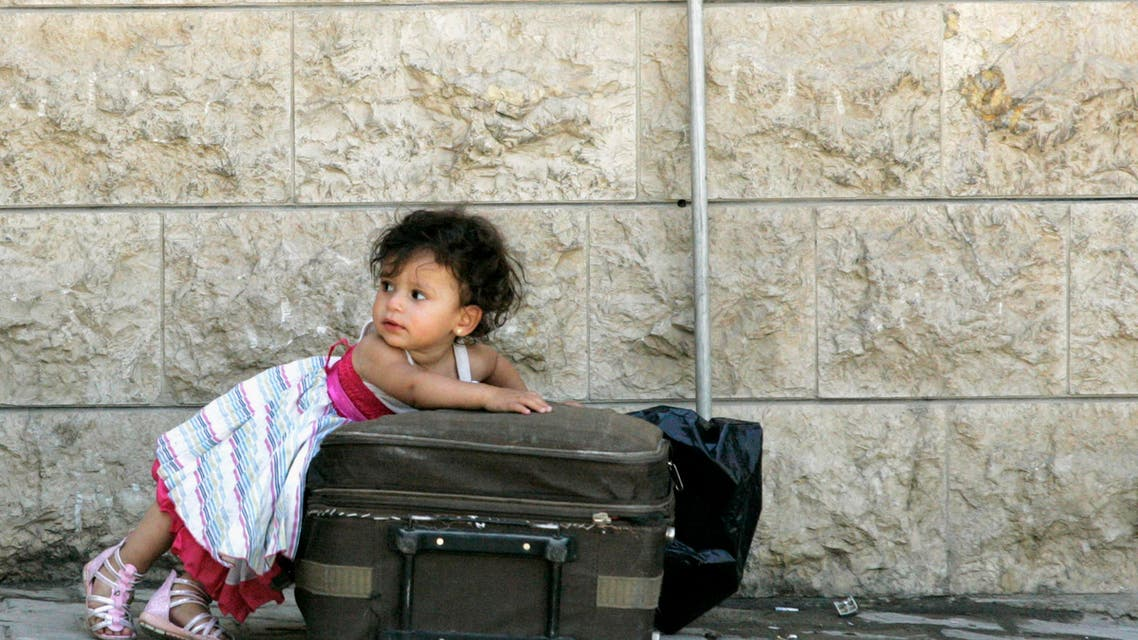 A Syrian girl leans over a suitcase on the Lebanese-Syrian border town of al-Masnaa July 20, 2012. (Reuters)