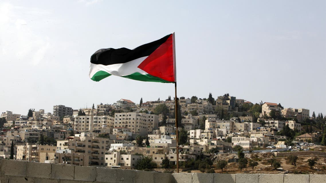 In this photo taken Tuesday, Oct. 20, 2015, a Palestinian flag flies on the roof of a temporary apartment that the Palestinian family family of Abu Nab has moved to, after being evicted from their apartment recently, in the Silwan neighborhood of east Jerusalem. AP