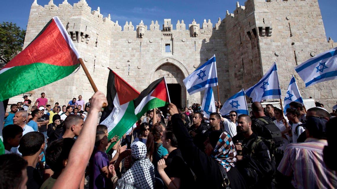 Israelis and Palestinians wave flags as Israelis march celebrating Jerusalem Day outside Damascus Gate in Jerusalem's old city. AP