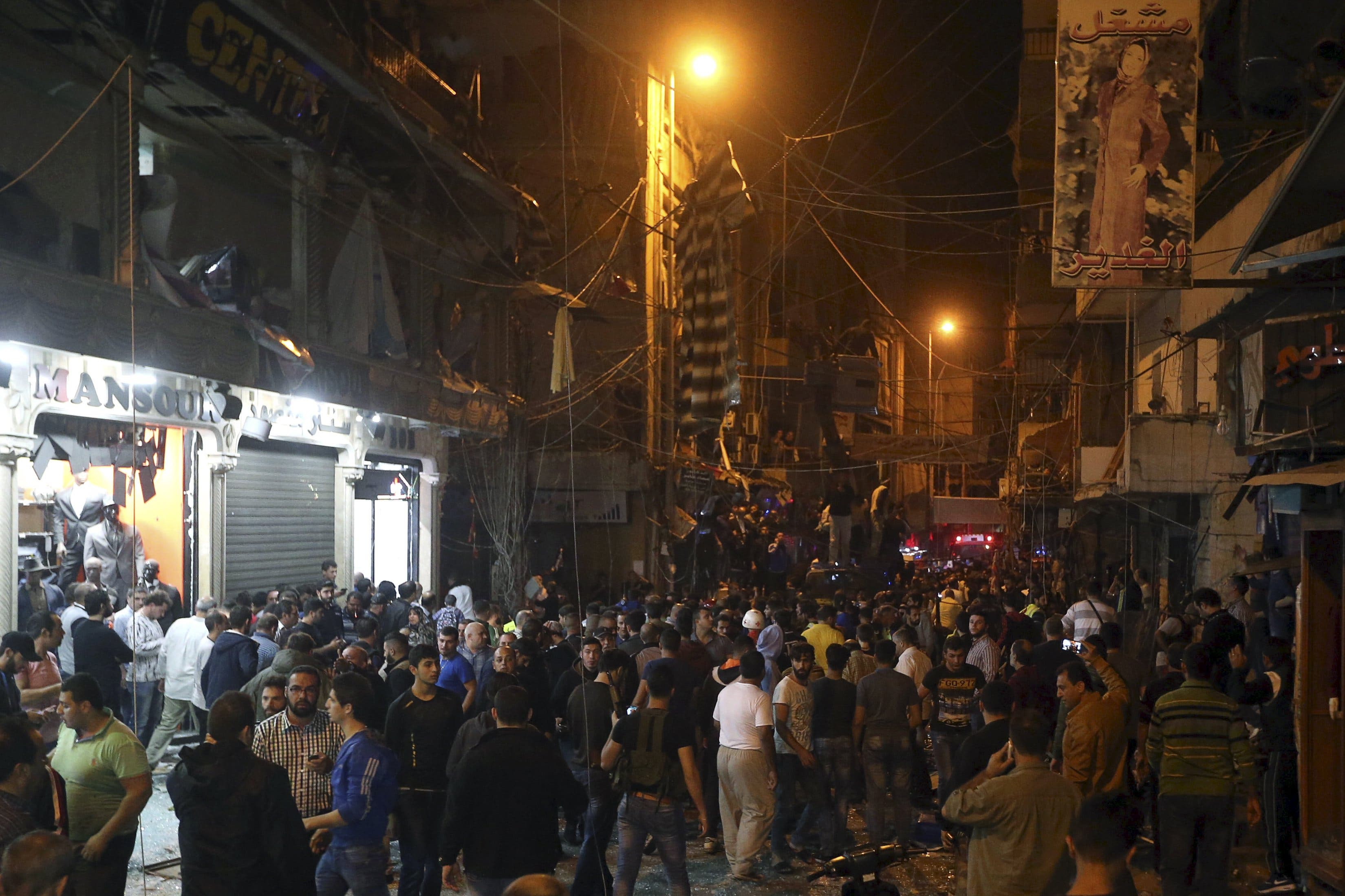 بیروت کے جنوبی علاقے میں بم دھماکوں کے بعد لوگ جمع ہیں۔