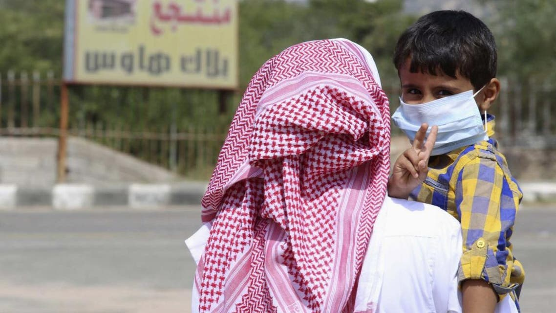A boy wearing a mask is held by his father in Taif June 7, 2014. (File photo: Reuters)