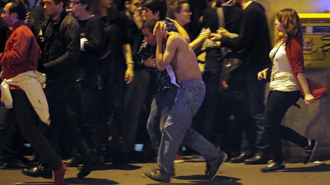 An injured man holds his head as people gather near the Bataclan concert hall following fatal shootings in Paris, France, November 13, 2015.  (Reuters)