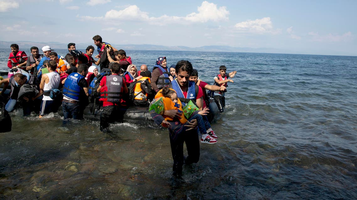 A man carries a child as migrants and refugees arrive on a dinghy after crossing from Turkey to Lesbos island, Greece, Tuesday, Sept. 8, 2015. (File photo: AP)