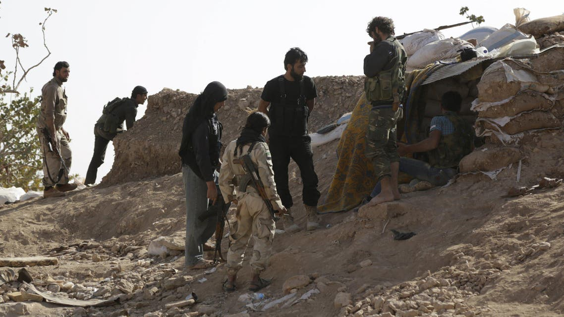 Free Syrian Army fighters of the 101 Division stand behind sandbags near the town of Morek in the northern countryside of Hama, Syria October 14, 2015. Supported by two weeks of air strikes, the Syrian army and its allies have been fighting insurgents in northern Hama province, and neighbouring Idlib and Latakia provinces, trying to reverse rebel gains over the summer which had threatened the coastal heartlands of Assad's Alawite minority. REUTERS/Khalil Ashawi