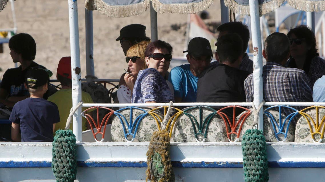 Western tourists peer out of a traditional ferry as they cross to visit the Valley of the Kings in Luxor, Egypt, Thursday, Nov. 5, 2015.