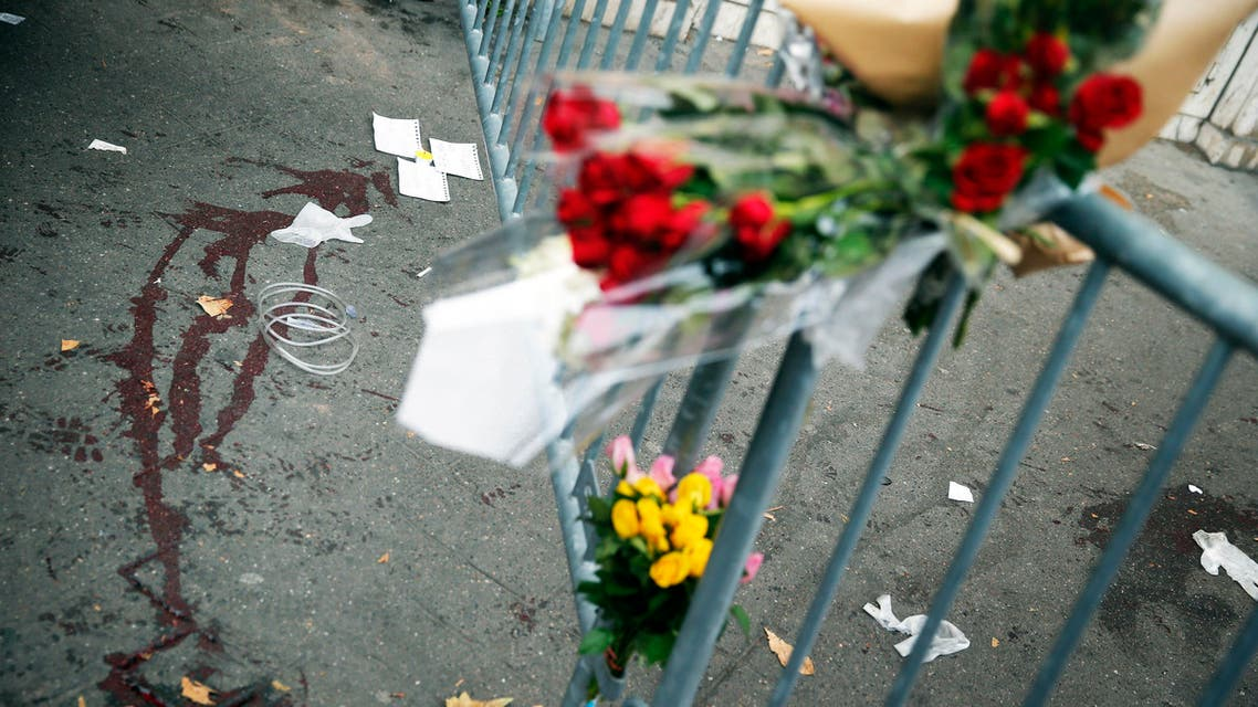 Flowers are placed outside the Bataclan concert hall, Saturday, Nov. 14, 2015 in Paris. French President Francois Hollande said more than 120 people died Friday night in shootings at Paris cafes, suicide bombings near France's national stadium and a hostage-taking slaughter inside a concert hall. (AP Photo/Christophe Ena)