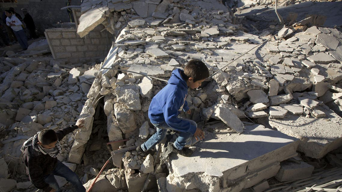 Palestinian youths walk on the rubble of a house that was demolished by the Israeli army in the village of Silwad, near the West Bank city of Ramallah, Saturday, Nov. 14, 2015. The Israeli military says it has demolished the homes of four Palestinians who carried out deadly attacks against Israelis. (AP Photo/Majdi Mohammed)