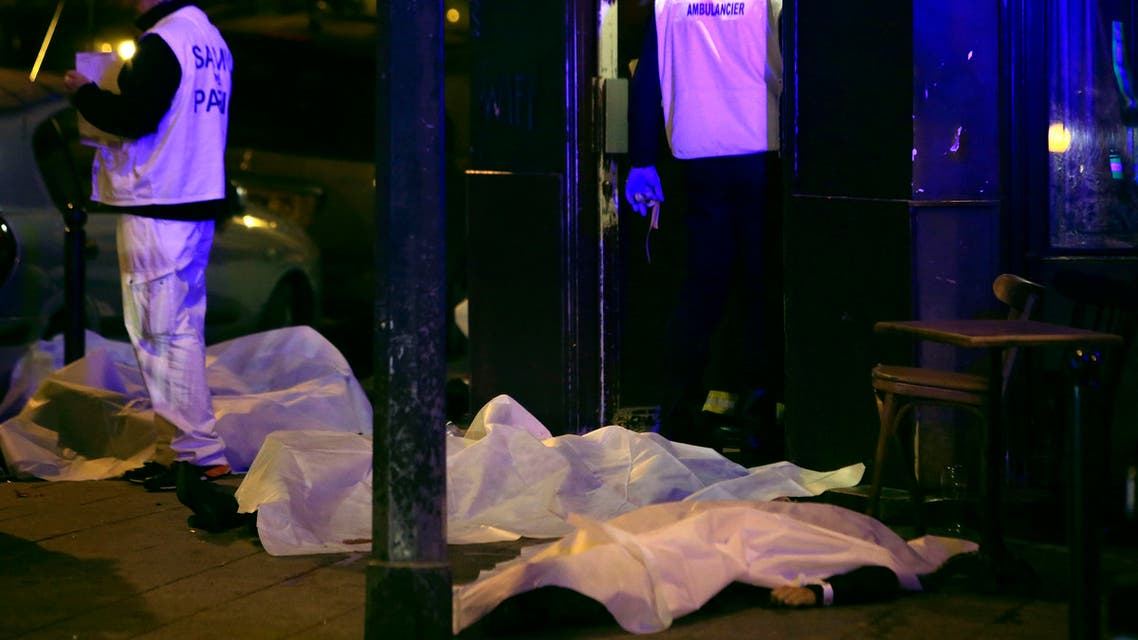 Victims lay on the pavement in a Paris restaurant, Friday, Nov. 13, 2015. Two police officials say at least 11 people have been killed in shootouts and other violence around Paris.