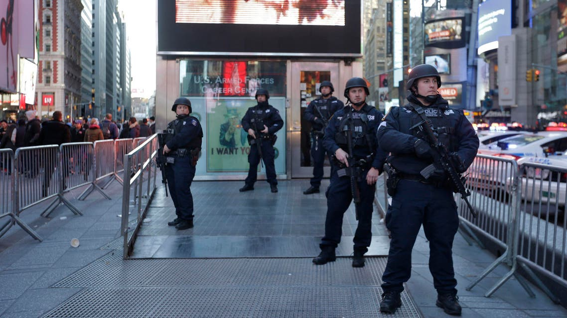 Heavily armed New York city police officers with the Strategic Response Group stand guard at the armed forces recruiting center in New York's Times Square, Saturday, Nov. 14, 2015.