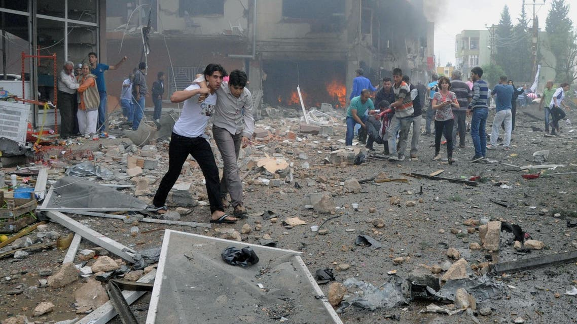 People carry injured people from one of explosion sites after several explosions killed at least 40 people and injured dozens in Reyhanli, near Turkey's border with Syria, Saturday, May 11, 2013, AP
