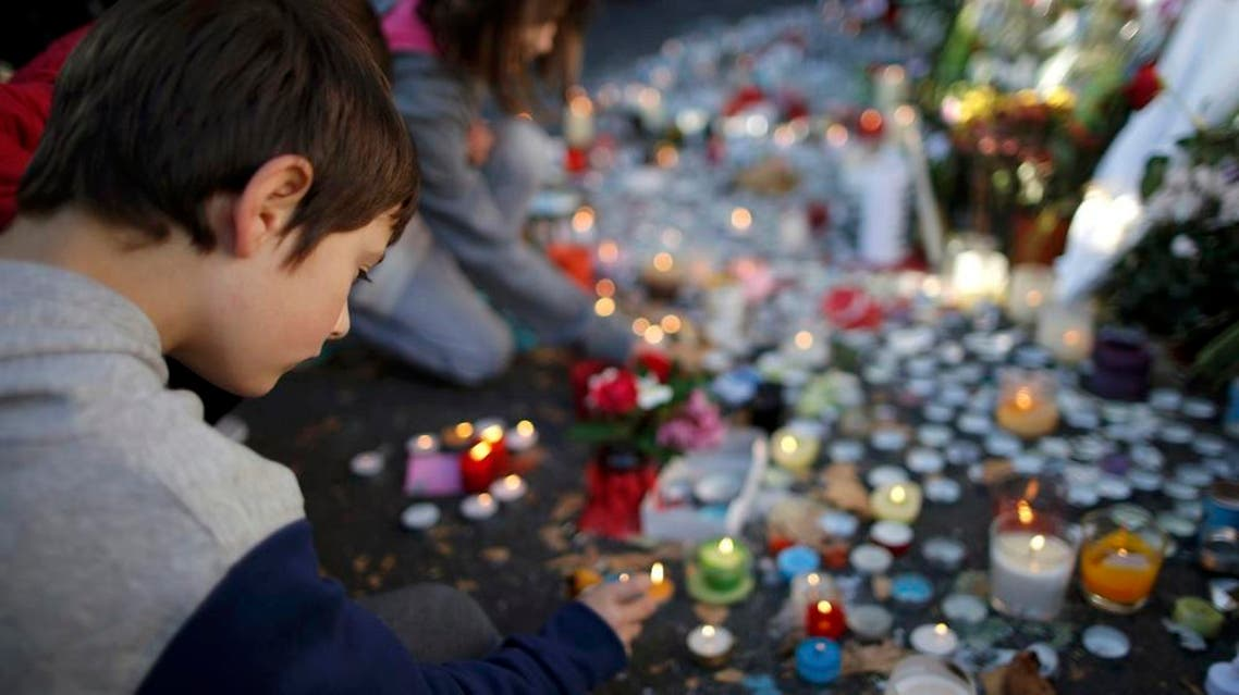 Children light candles near the site of the attack at the Bataclan concert hall in Paris, November 15, 2015. (Reuters)